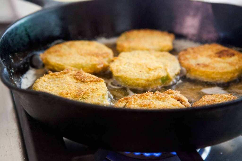 tomates vertes frites dans un poêlons sur le feu.