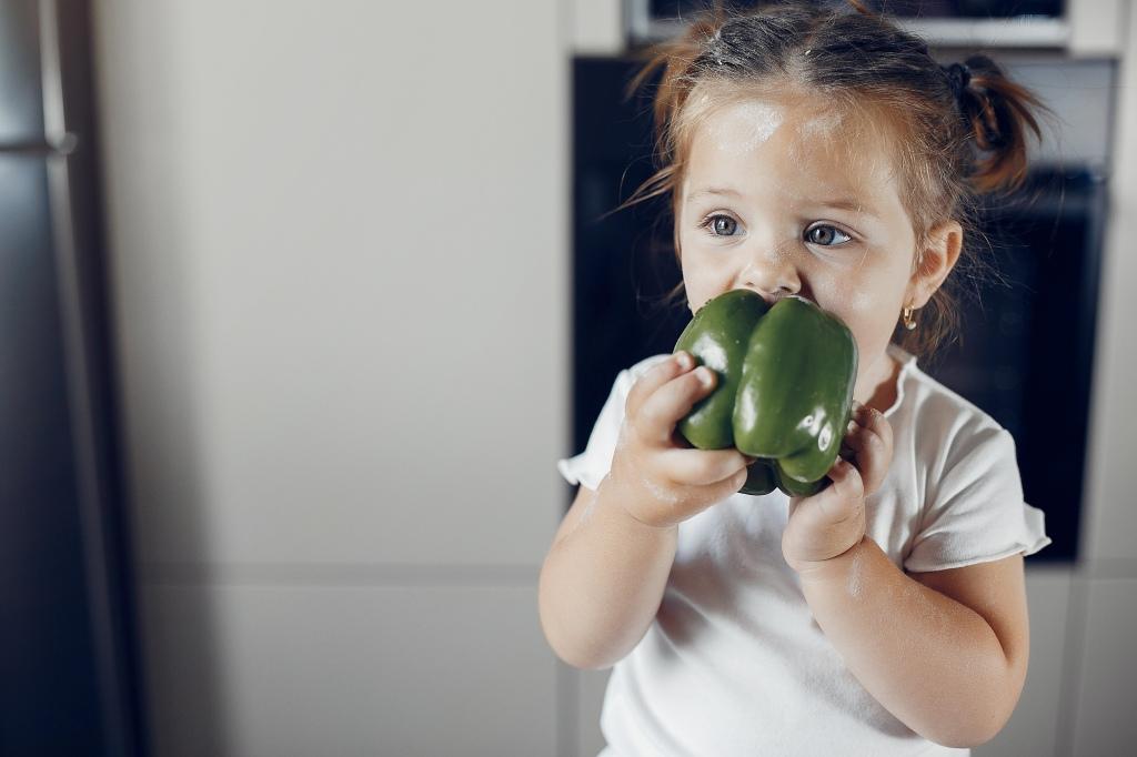Petite fille mangeant un poivron vert. Cuisine blanche.