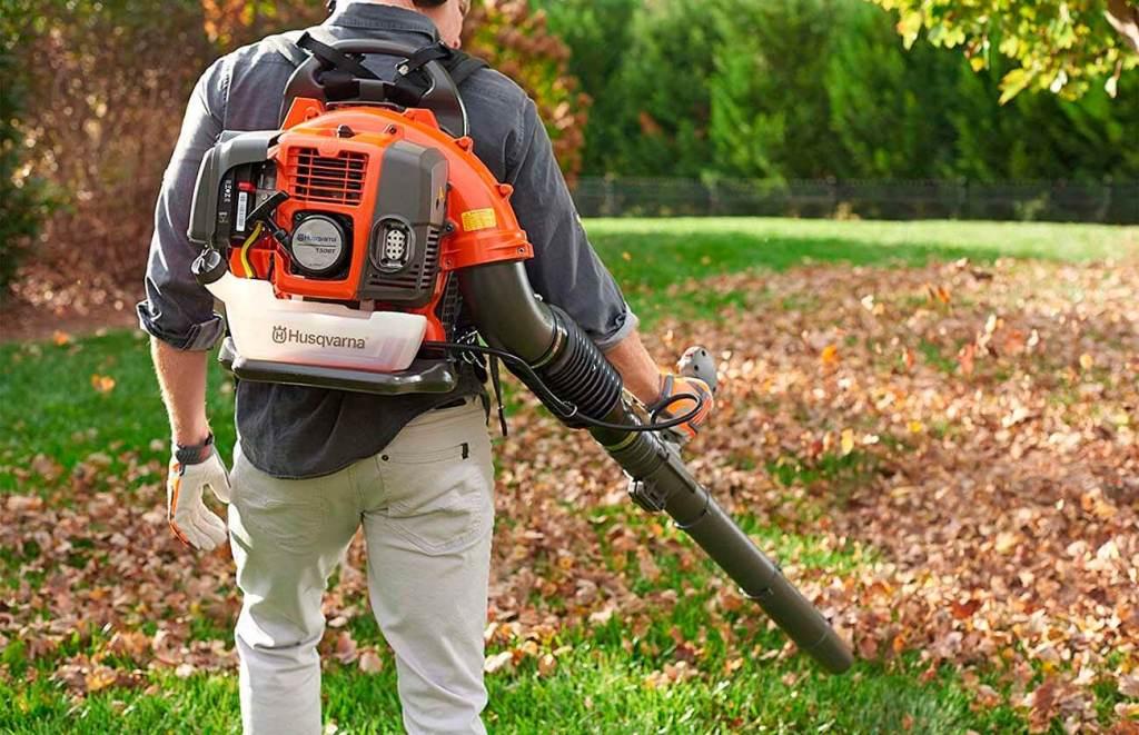Souffleuse à feuilles qui pousse des feuilles mortes sur un gazon.