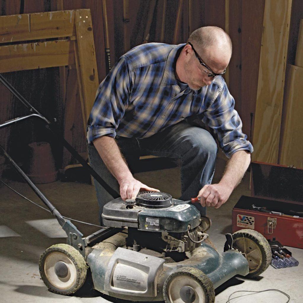 Homme qui répare une tondeuse.