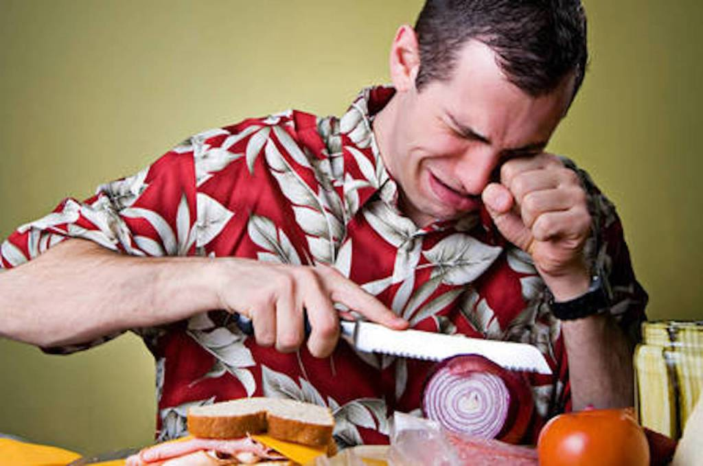 Homme qui pleure en tranchant un oignon.